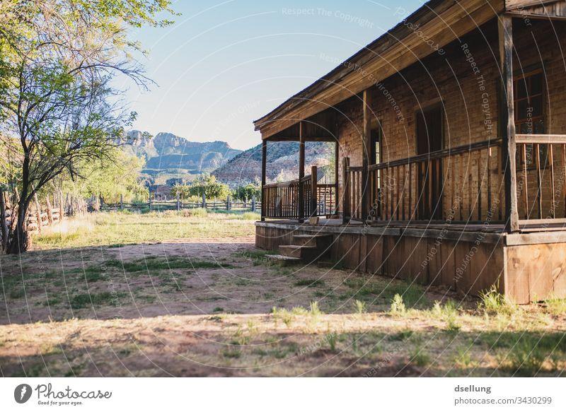 Holzveranda eines Backsteinhauses im Abendlicht ruhig Einfachheit Geisterstadt Sonne Starke Tiefenschärfe Einsamkeit alt braun Gegenlicht Spuren Sonnenstern