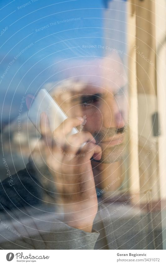 Junger Mann am Telefon Glas Mobile Menschen Funktelefon modern Business Fenster Kaukasier männlich Drahtlos benutzend Geschäftsmann Erwachsener Porträt