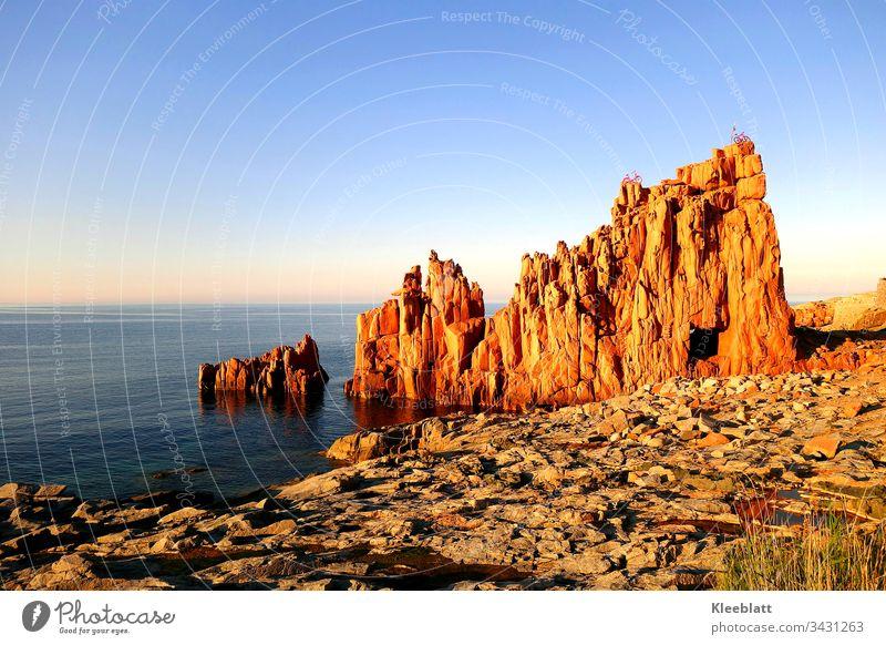 Roter Fels am Meer Roter Fels mit Durchblick zum Meer Felsen mit Fahrräder Strand Urlaub Abendstimmung blauer Himmer Meerblick Attraktion am Meer