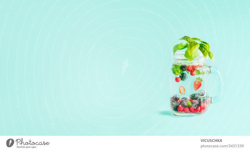 Beeren entgiften Früchte in einem mit Kräuterblättern aromatisierten Mason-Glas auf dem Tisch auf sonnigem türkisblauem Hintergrund. Sommerliche Stimmungsdrinks und Lebensstil. Gesunder Hintergrund