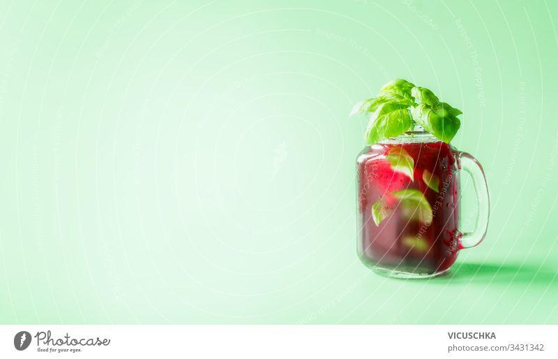 Limonade mit roten Beeren im Mason-Glas, gewürzt mit Kräuterblättern auf sonnig-hellem, minzgrünem Hintergrund. Sommerliche Stimmung.  Gesunde Getränke und Lebensweise. Raum kopieren