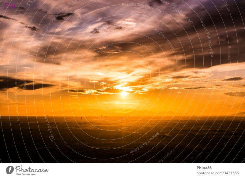 Sonnenuntergang über der amerikanischen Grenzstadt El Paso, wobei die Wassertürme besonders hervorstechen. Im Hintergrund sieht man eine Bergkette aus dem benachbarten Mexiko. Aufgenommen aus dem Roten Sand am östlichen Rand der Stadt.