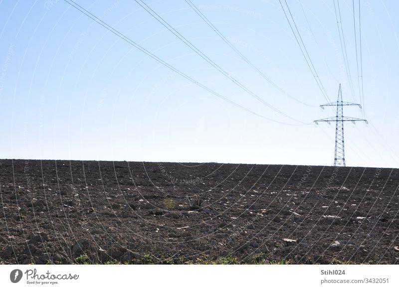Hochspannungsmast steht auf Entfernung einsam auf gepflügtem Acker Strommast Stromversorgung Landwirtschaft Horizont Winter allein Trassenführung Landschaft