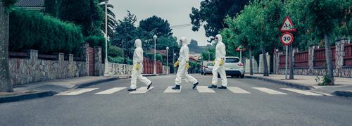 Menschen in bakteriologischen Schutzanzügen, die eine leere Straße entlanglaufen bakteriologischer Schutzanzug covid-19 Coronavirus Sperrstunde Quarantäne Virus