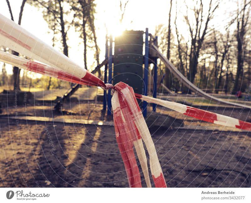 Nahaufnahme des Absperrbandes vor einem Spielplatz Korona Virus Schloss Ausfahrt leer zu Hause Aufenthalt Klebeband Barriere Park Kind Spaß Frühling Sommer