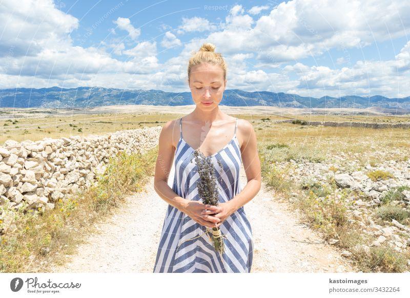 Kaukasische junge Frau in Sommerkleidung mit Lavendelblütenstrauß, die im Sommer die reine mediterrane Natur an der felsigen kroatischen Küstenlandschaft auf der Insel Pag genießt