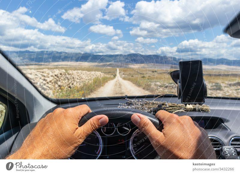 Detail der Hände des männlichen Fahrers am Lenkrad. Fährt ein Auto auf der Landstraße. Blick aus der Kabine durch die Windschutzscheibe. PKW Armaturenbrett