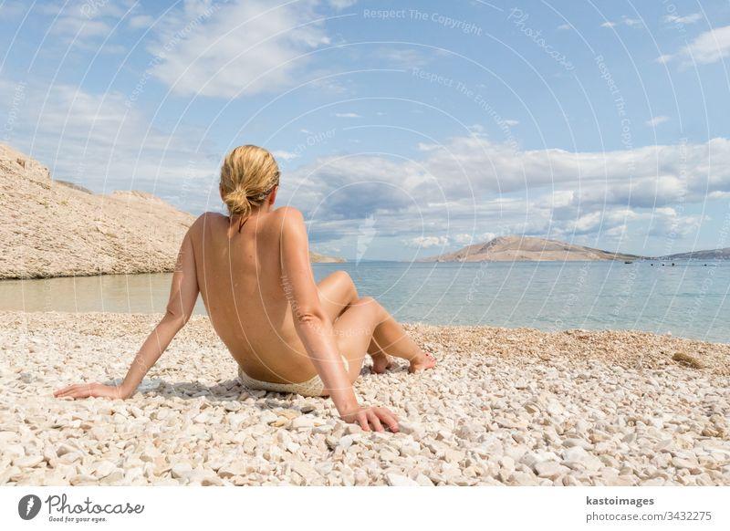 Rückansicht einer sexy jungen kaukasischen Frau, die sich oben ohne auf einem abgelegenen Pabble Beach auf der Insel Pag, Kroatien, im Mittelmeer sonnen. Strand