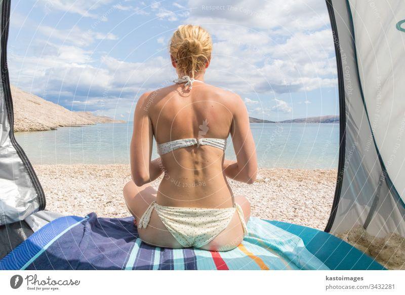 Rückansicht einer schönen jungen kaukasischen Frau, die die Sommersonne am Mittelmeerstrand genießt und durch ein Schattenzelt vor Hitze und Sonnenbrand geschützt ist.