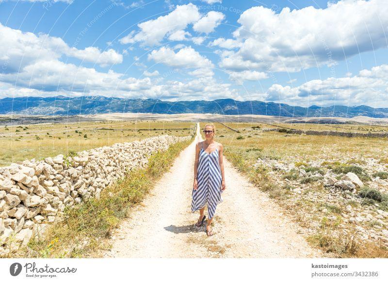 Kaukasische junge Frau in Sommerkleidung hält einen Strauß Lavendelblüten in der Hand, während sie im Sommer durch die trockene, felsige Landschaft der kroatischen Mittelmeerküste auf der Insel Pag spaziert