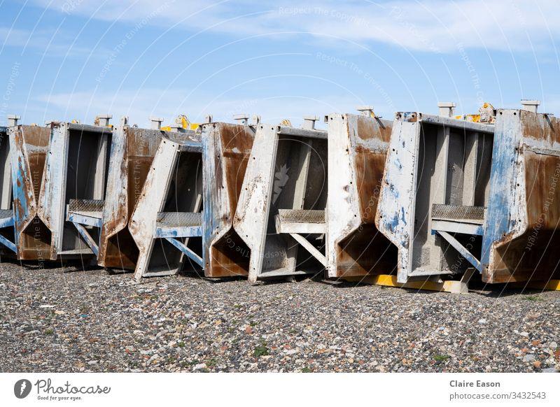Schwere, nicht spezifische Produktionsanlagen, die draußen auf einer Kiesfläche mit blauem Himmel aufgereiht sind. Betriebsausstattung Fabrikmaschinen Werkhof
