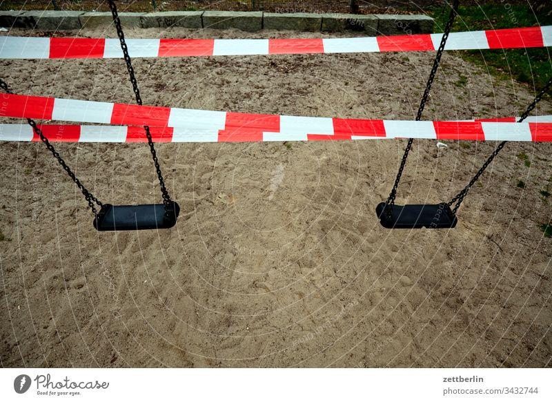Gesperrte Schaukel auf dem Spielplatz absperrband absperrung ausgangssperre außen corona covid covid 19 flatterband hygiene isolation menschenleer seuche