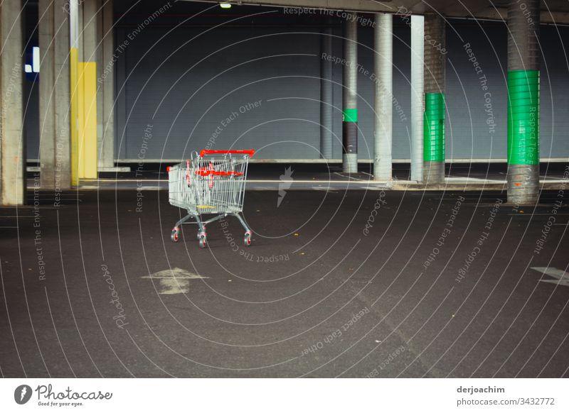 """Einkaufswagen im leeren  Park - Deck . Einfahrt Markierung """" links """" Parkdeck Parkplatz Architektur Beton Verkehrswege Pfeil Linie Menschenleer Wand Parkhaus"""