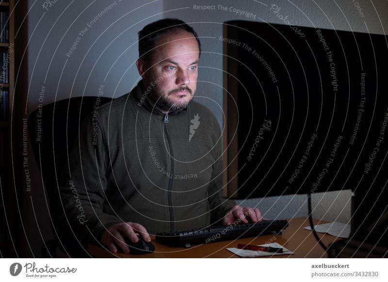 Mann der nachts im Homeoffice vor dem Computer sitzt pc Bildschirm Schreibtisch Technik & Technologie Internet Sitzen Arbeit Büro online Monitor Desktop Sucht