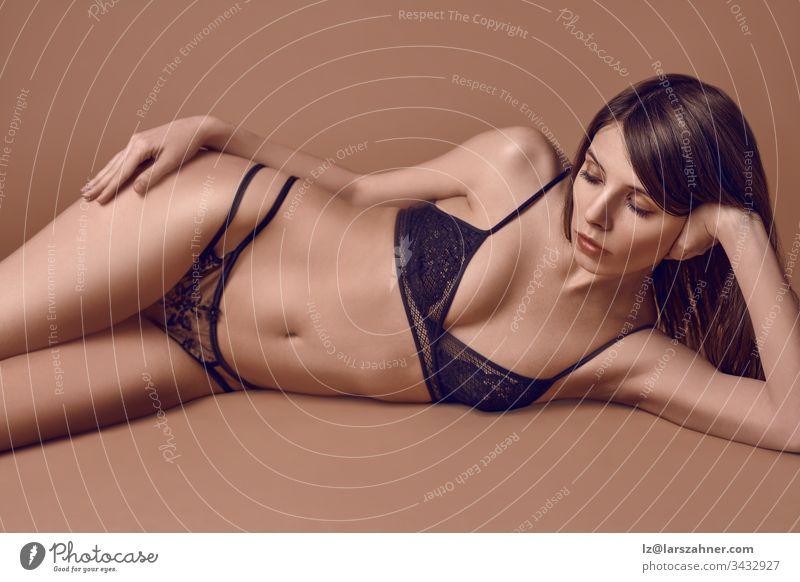 Sexy, schlanke junge Frau in schwarzer Unterwäsche, die auf der Seite auf einem braunen Studiohintergrund liegt und der Kamera einen ernsthaft schwülen Blick verleiht
