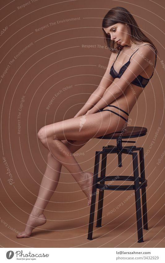 Sexy schlanke junge Frau sitzt elegant auf einem Hocker in schwarzer Unterwäsche in einer Seitenansicht auf braunem Porträt, während sie sittsam auf ihre Hände blickt, die zwischen ihren nackten Beinen mit Kopierraum gefasst sind.