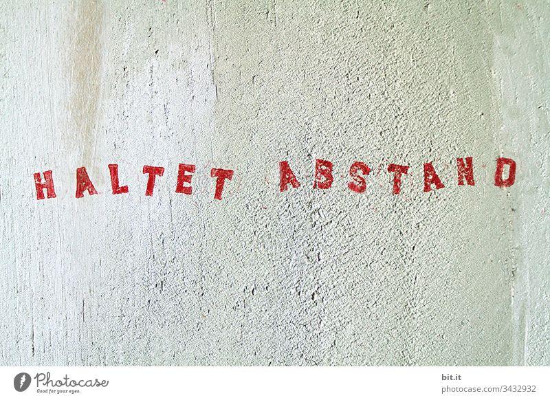 Haltet Abstand, Schriftzug gestempelt in Rot auf weisser Wand. Gefahr Hinweis Epidemie Schützen Hinweisschild COVID Quarantäne Prävention Coronavirus Ansteckend