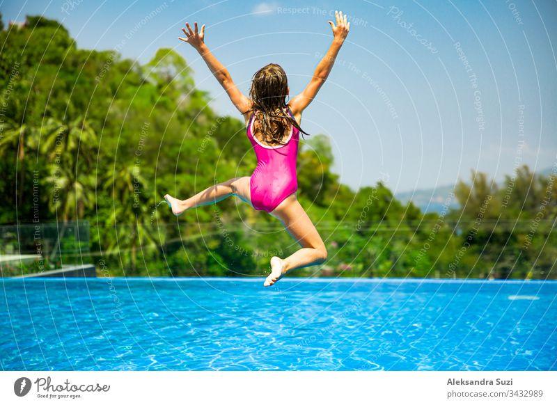 Aufgeregtes, lustiges, kleines Mädchen, das zum Swimmingpool springt. Fröhliche Sommerferien aktiv Abenteuer Asien blau offen sorgenfrei heiter Kind Kindheit