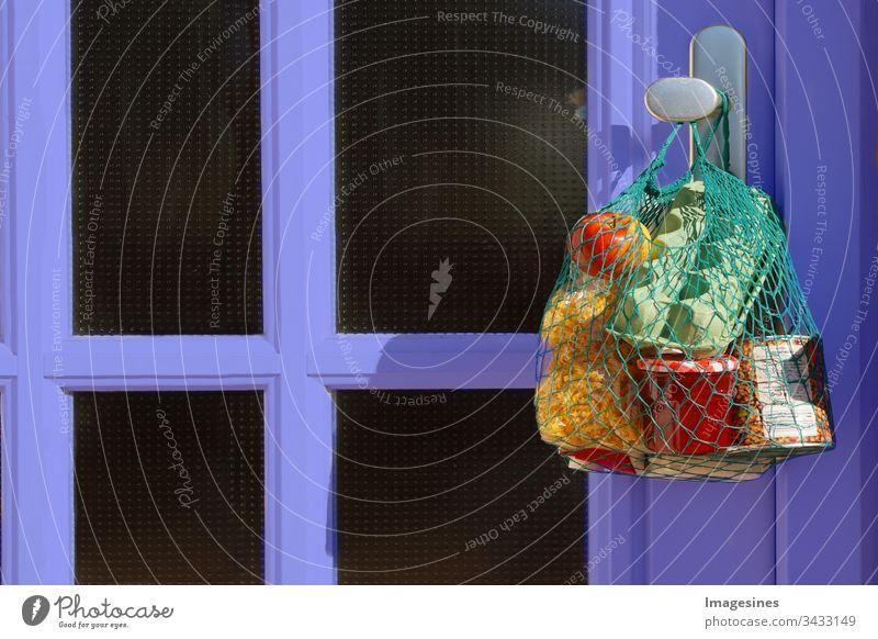 kontaktloser Einkauf Lieferung während der Quarantäne. Einkaufstasche mit Waren und Lebensmitteln hängt an der Haustür, Nachbarschaftsunterstützung - Konzept zur Quarantänezeit wegen Coronavirus-Infektion Covid-19