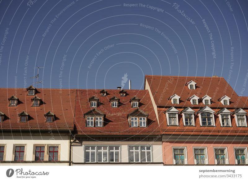 drei Häuserdächer mit verschieden großen Fenstern darin eine Fensterzeile kleine Fenster im Dach blauer Himmel 3 Schindeldächer rot Fenster mit Streben