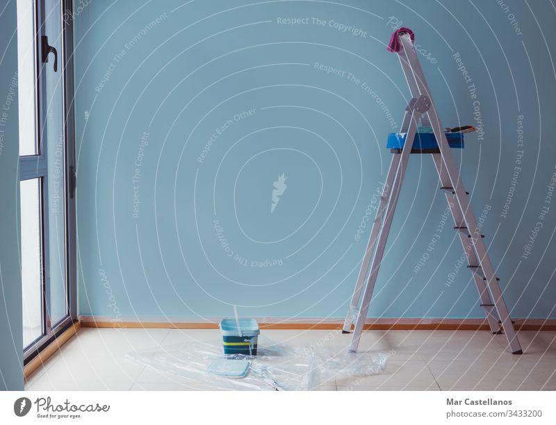 Malertreppe mit frisch gestrichenem blauen Wandgrund. Arbeiten im Haus. Raum zum Kopieren. Anstreicher Treppenhaus Malerei Tablett Blauer Hintergrund