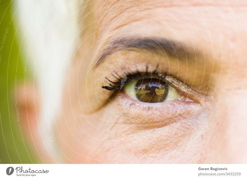 Gefaltetes Auge einer schönen Frau Wimpern Erwachsener Lebensalter braun Pflege Nahaufnahme Detailaufnahme älter Ausdruck Augenbraue Gesicht Aussehen Makro