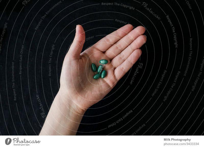 Leuchtend grüne Pillen in einer menschlichen Hand Nahaufnahme Schmerztabletten sortiert Antibiotikum Vitamin Ergänzung Abhilfe Verschreibung Tablette Apotheke