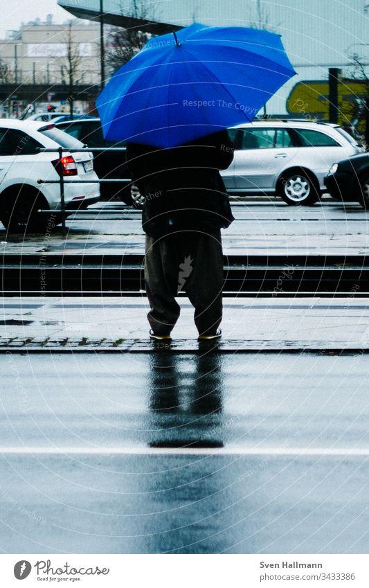 Mann mit blauem Regenschirm wartet Blau regenschirm mann baggy Haltestelle autos warten Mensch Erwachsene schlechtes Wetter Farbfoto Außenaufnahme nass Wasser