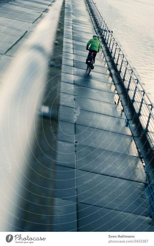 Einsamer Fahrrad Fahrer an Promenade Bike radler wasser weg jacke Außenaufnahme Straße Fahrradfahren Sport Verkehr Wege & Pfade Verkehrsmittel Straßenverkehr
