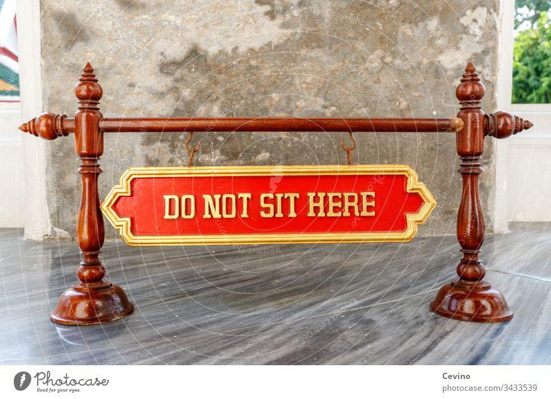Schild Do not sit here Warnung Anweisung Verbot Mahnung Tempel Buddha Buddhismus buddhistisch Religion Glaube Aberglaube Roter Hintergrund Gold Marmorboden