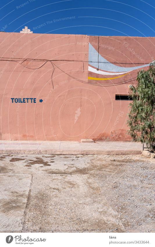 Toilette Wegweiser in Marokko Haus Fasseade Schrift Bedürfnis Pfeil Richtung Menschenleer Hinweis Orientierung Empfehlung Navigation rechts Wege & Pfade