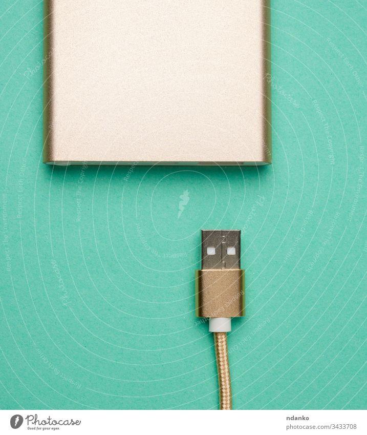 goldenes netzteil und kabel mit usb-anschluss zum aufladen mobiler geräte auf grünem hintergrund Kabel Schnur Hintergrund Bank Ladegerät Energie Mobile Kraft