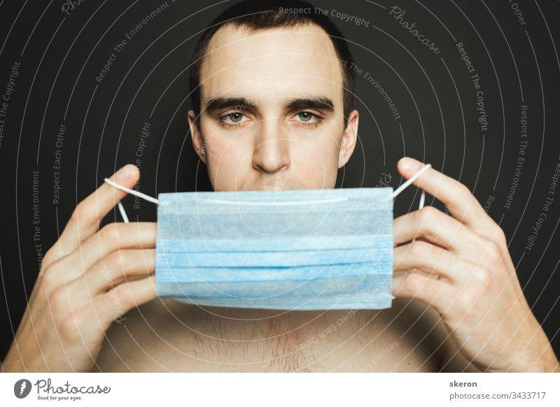 Porträt eines Mannes mit medizinischer Gesichtsmaske, der sich um die Prävention des pandemischen Coronavirus auf grauem Hintergrund kümmert. Quarantäne- und Pandemiekonzept. Mann mit aseptischer Maske zur Krankheitsprävention.