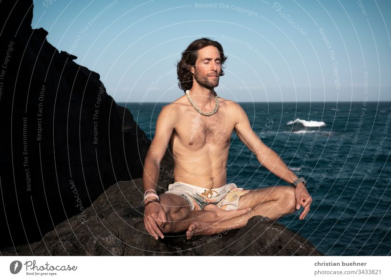 junger mann am meer in yoga position nackt lange haare 35 jahre fels badehose hippie blauer himmel sport wellness relax urlaub frieden ruhe pilates