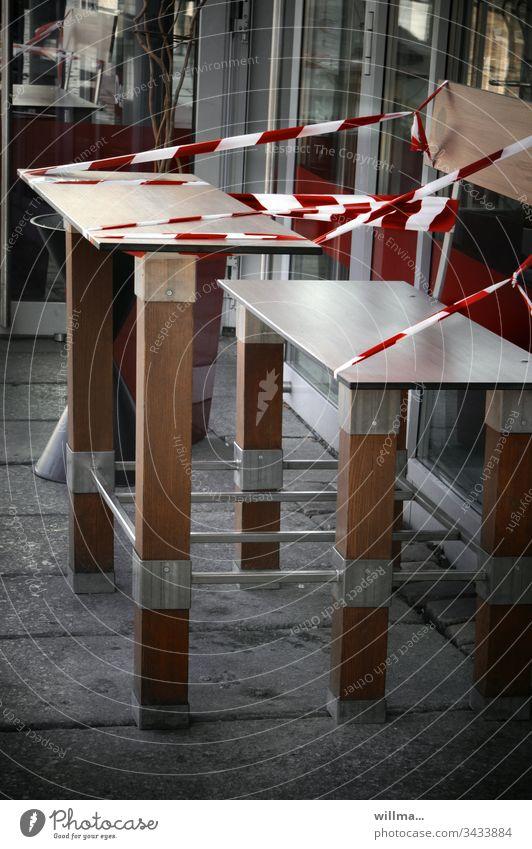 Mit Flatterband angesperrte Sitzgruppe vor einem Bistro, Bäcker oder Straßencafé Bank Tisch abgesperrt Absperrband Schutz Einschränkung des öffentlichen Lebens