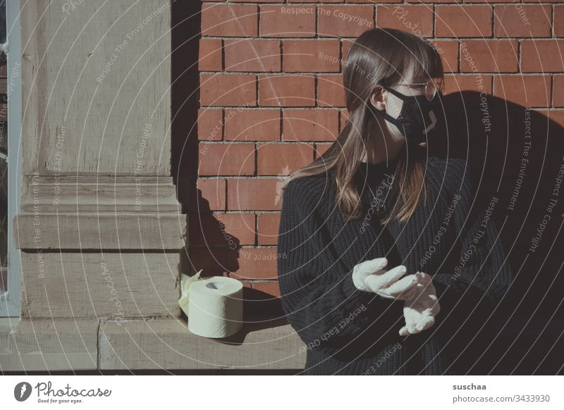 jugendliche mit mundschutz an einer hauswand mit klopapier | corona thoughts Teenager Jugendliche junge Frau Zuhause Homeoffice Brille zu Hause bleiben Krise