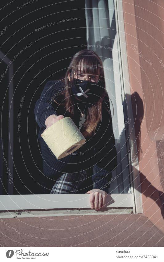 jugendliche mit mundschutz am fenster mit einer rolle klopapier | corona thoughts Teenager Jugendliche junge Frau Zuhause Homeoffice Brille zu Hause bleiben