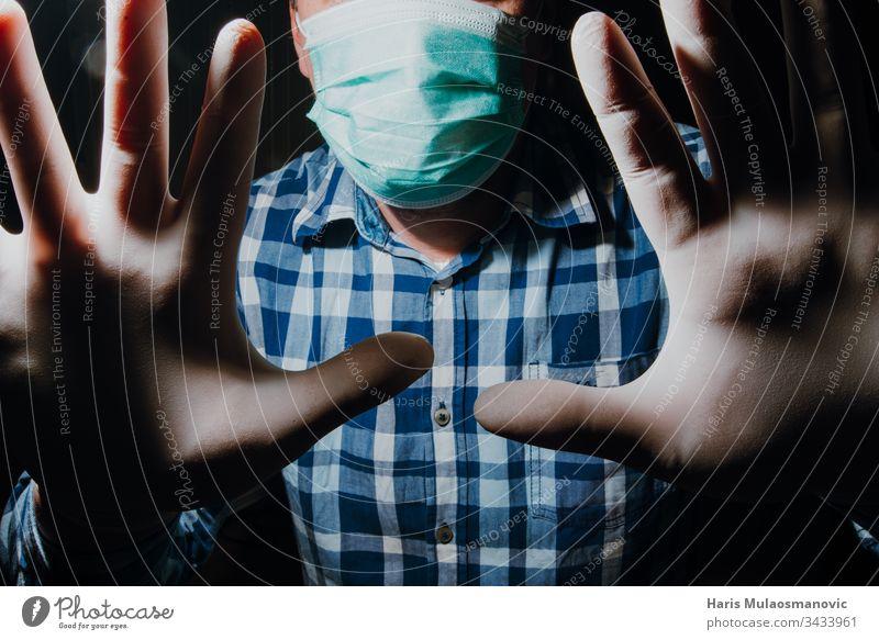 Mann soziale Distanzierung mit Maske und medizinischen Handschuhen zum Schutz vor dem Coronavirus covid-19 Erwachsener apokalyptisch Hintergrund schwarz