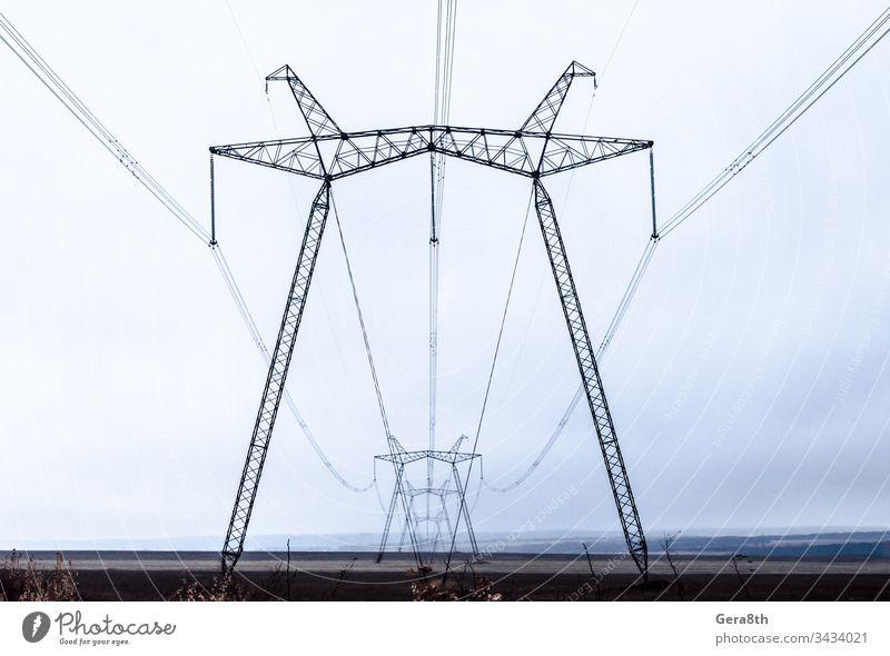 Hochspannungsleitungen in der Perspektive Herbst Wolken Konstruktion Schnur dunkler Himmel elektrisch Energie Abend industriell Linien Metall Pole Kraft