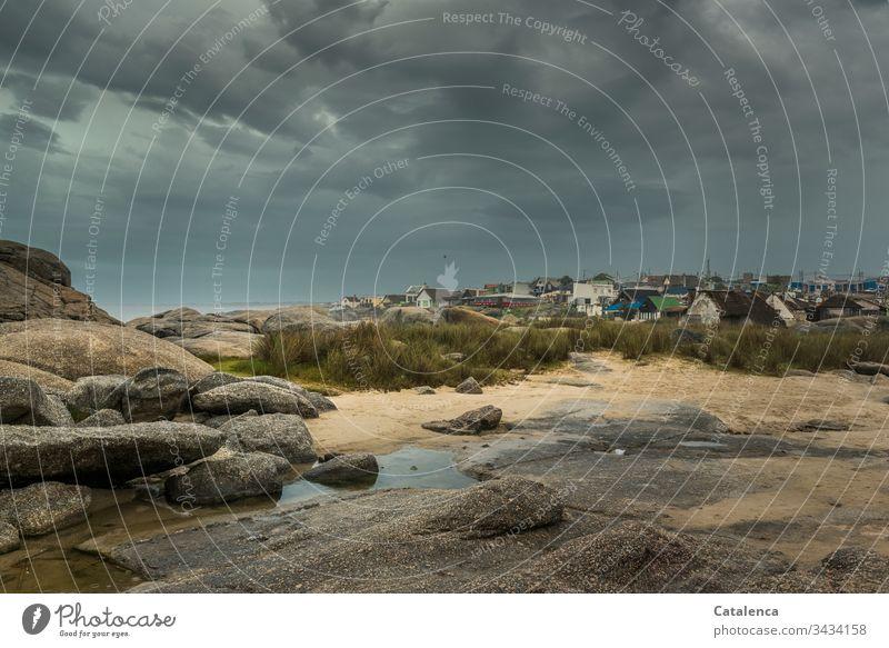 Dunkle Gewitterwolken türmen sich über das Dorf am Strand Natur Wetter Wolken Klimawandel Umwelt Strurmtief Regen schlechtes Wetter Küste Sand Felsen