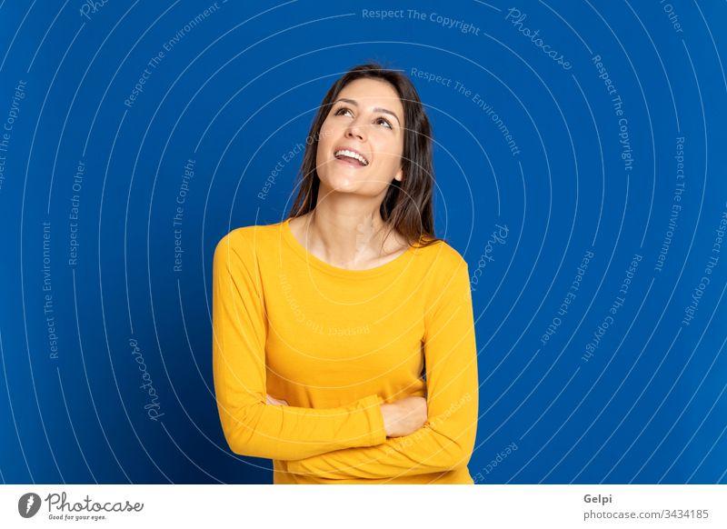 Brünettes Mädchen mit gelbem T-Shirt Person blau Glück nachdenklich besinnlich Denken sich[Dat] einbilden Vorstellungskraft Idee Lösung Zweifel zweifelhaft klug