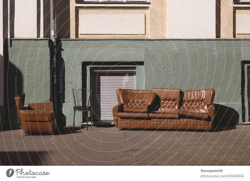 Braune Möbel stehen verlassen vor einem Haus mit runterlassenen Rolladen Sperrmüll keine Menschen Sessel Sofa draußen kaputt Stadt weggeworfen Sitz Müll Abfall
