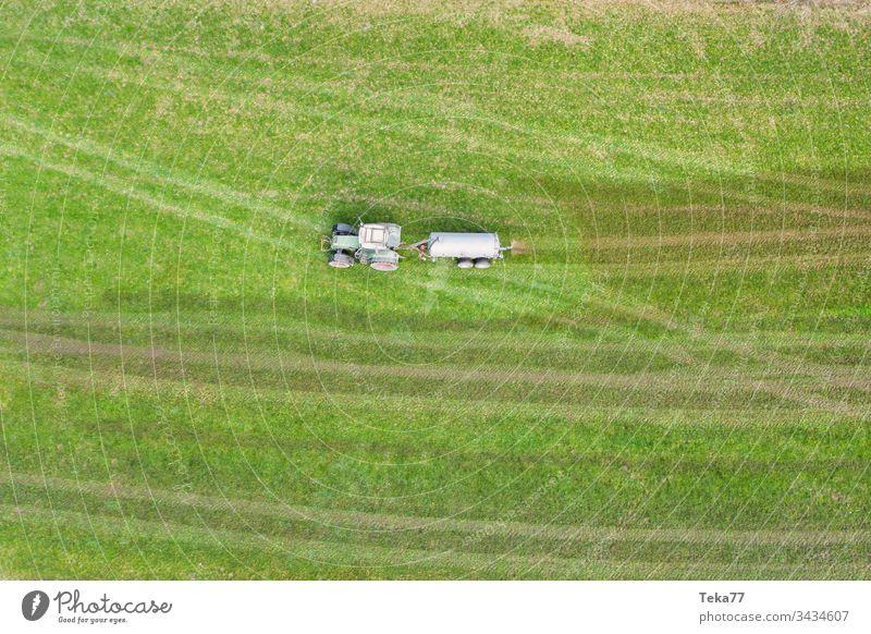 Traktor, der Kuhdung von oben besprüht Ackerschlepper Landwirtschaft Bauernhof Ackerbau landwirtschaftlich Wiese Feld Gras modern moderne Landwirtschaft