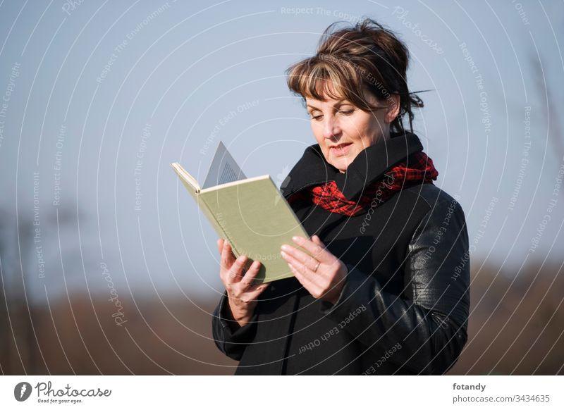 woman reading upper part 50s mittleres Alter Entspannung Frau Lederjacke Park allein Buch Draussen eine erwachsen zufrieden Ablenkung freizeit modisch Jacke