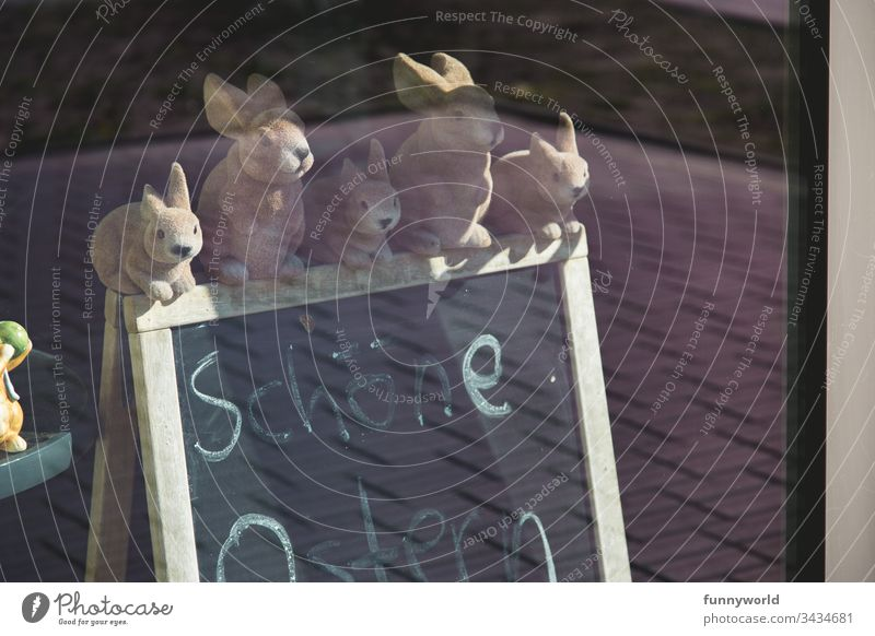 5 Osterhasen - figuren sitzen auf einer Tafel, auf der Frohe Ostern steht. Hase Dekoration Fenster Frühling abgesagt geschlossen einsam traurig handgeschrieben