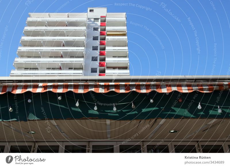 lichterkette, markise und hochhaus gebäude balkon balkone fassade architektur immobilie zuhause zu hause wohnen leben mieten wohnung wohnungen balkonien sonne