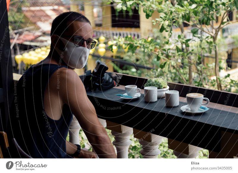 Ein Mann mit Gesichtsmaske sitzt in einem Café im Ausland, wo er wegen des Coronavirus gestrandet ist Covid Covid-19 Tourist Leben Urlaub Asien Kaffee Sonne