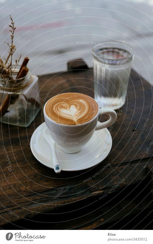 Eine Tasse Cappuccino mit einem Latte Art Herz auf einem Holztisch in einem Café Kaffee latte art Tisch TischHolztisch Getränk Frühstück braun Farbfoto Koffein