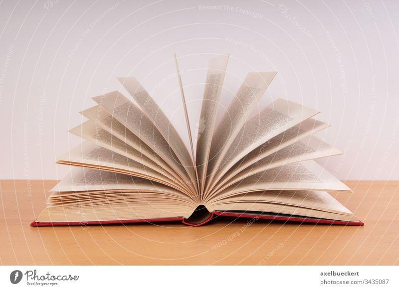 ein offenes Buch Hardcover Seiten Literatur Bildung Wissen Weisheit lesen Lernen altmodisch Schreibtisch Tisch Objekt Information Schule Universität Bibliothek