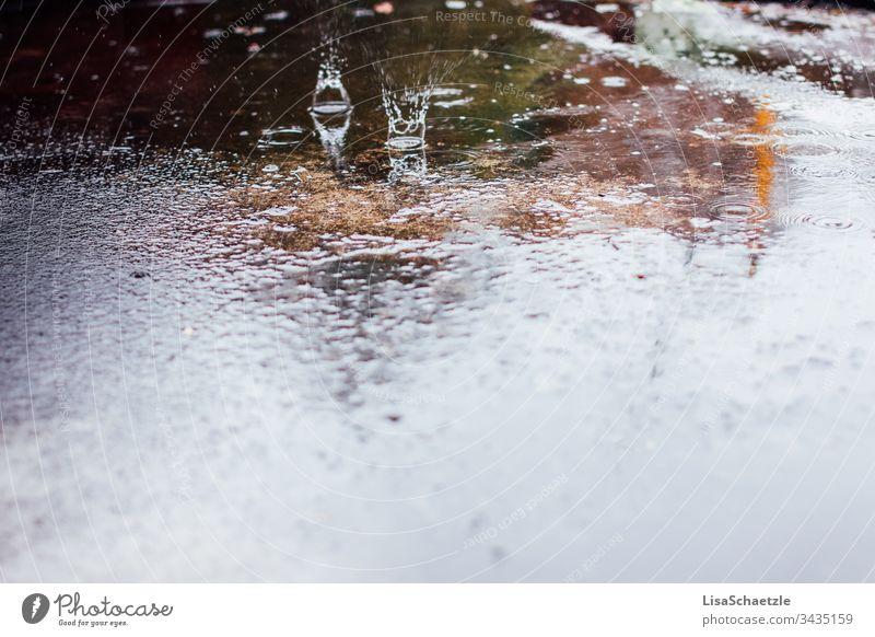 Wassertropfen treffen auf nassen Asphalt auf. Ein regnerischer Tag auf der Straße. regen wasser spiegelung boden beschaffenheit abstrakt wand kalt blau dekor